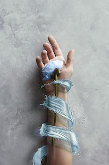 Fiore blu a portata di mano con spruzzi d'acqua blu su sfondo grigio pietra. concetto di arte