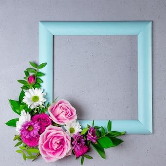 Cornice blu decorata con bellissimi fiori estivi con spazio vuoto per foto quadrata di testo