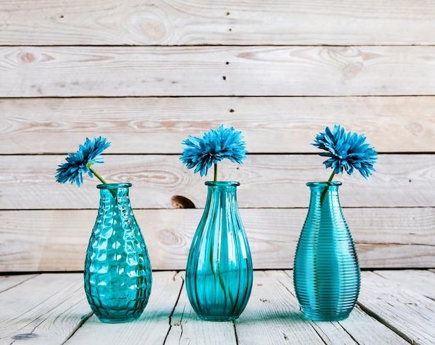 Fiore blu della gerbera in un vaso su fondo di legno
