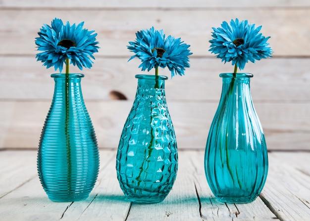 Fiore blu della gerbera in un vaso su legno