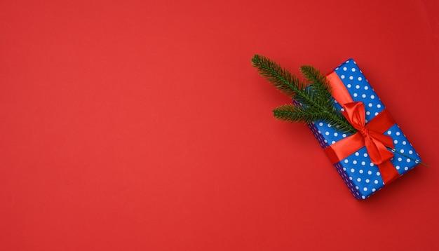 Confezione regalo blu legata con nastro rosso su sfondo rosso, vista dall'alto. sfondo festivo, copia spazio