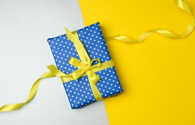 Confezione regalo blu legata con un nastro di seta gialla su sfondo grigio, vista dall'alto. sfondo festivo