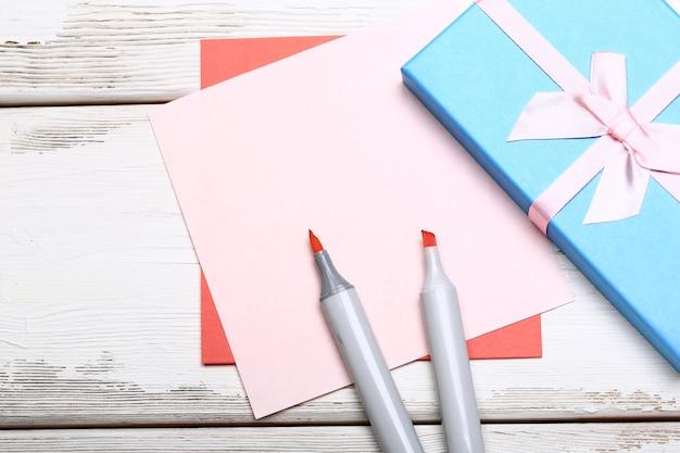 Confezione regalo blu con fiocco, pennarelli e fogli di carta colorati su fondo di legno bianco
