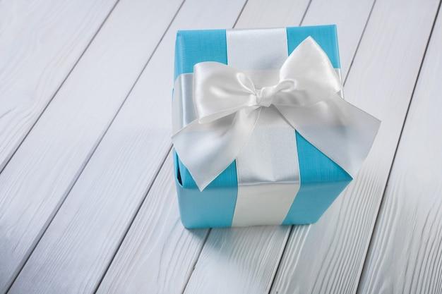 Scatola regalo blu con fiocco bianco su tavole di legno bianche