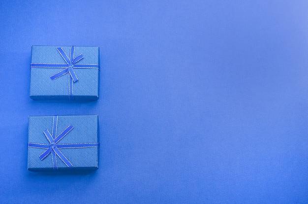Contenitori di regalo blu su sfondo blu con spazio di copia. regali per uomini per le feste.