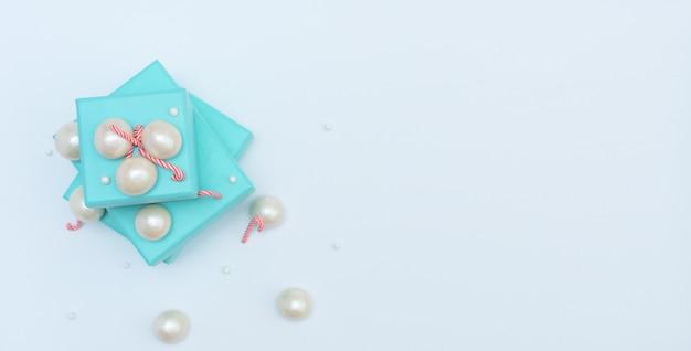 Scatole regalo blu con bastoncini di natale, perle grandi e piccole su bianco