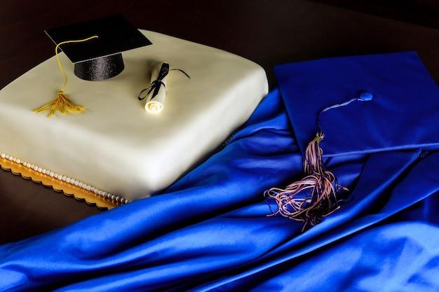 Abito da laurea blu e berretto con torta per la fine della scuola.