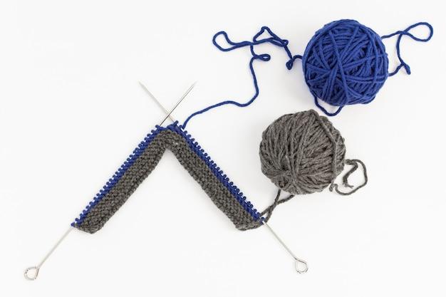 Gomitoli di lana blu e grigi con ferri da maglia sulla superficie bianca