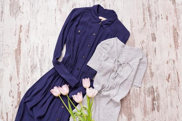 Abito blu e grigio, tulipani rosa su una superficie di legno