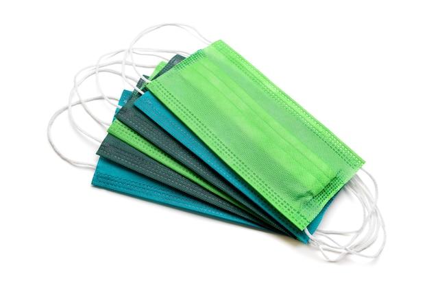 Maschere protettive luminose blu e verdi per la protezione delle vie respiratorie dall'infezione da coronavirus durante una pandemia e la conservazione dell'individualità