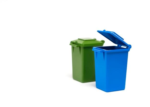 I bidoni della spazzatura blu e verdi si trovano su uno sfondo bianco closeup concetto di smistamento dei rifiuti