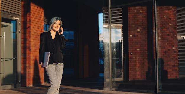 Donna di affari dai capelli blu che cammina nella strada e discutere sul telefono che tiene un computer portatile e sorridere