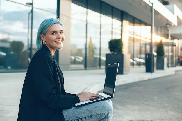 Donna di affari dai capelli blu che lavora al suo computer mentre posa davanti a un grande edificio