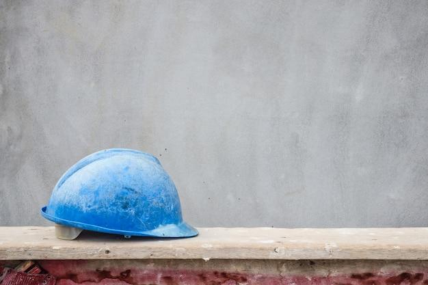 Cappello duro blu sul cantiere della costruzione della casa