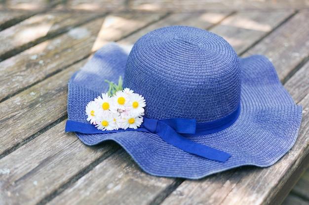 Cappello blu sdraiato su una panca di legno con un piccolo bouquet di margherite alla giornata di sole. bouquet di prato e fiori di campo. foto romantica di un periodo estivo carino. concetto di vacanza
