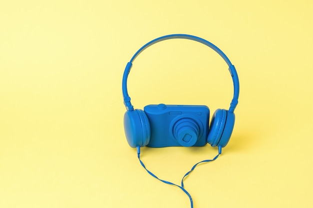 Cuffie blu e una fotocamera blu su sfondo giallo. attrezzatura elegante per riprese di foto e video.
