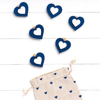 Cuore blu ed ecobag su superficie di legno bianca. concetto di san valentino.