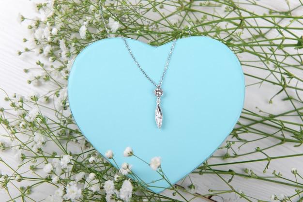 Scatola regalo a forma di cuore blu con elegante ciondolo su sfondo bianco con piccoli fiori bianchi, celebrazione di san valentino
