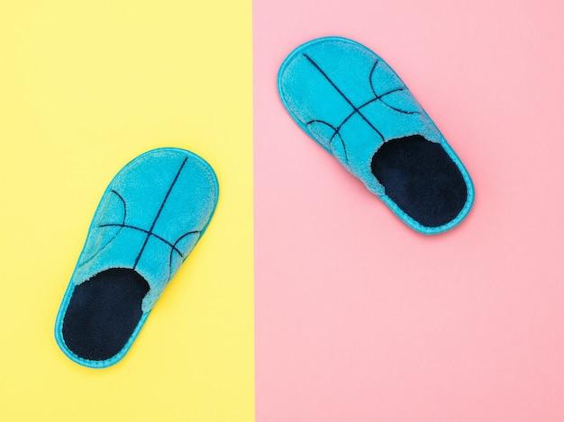 Pantofole blu della casa sulla superficie rosa e gialla