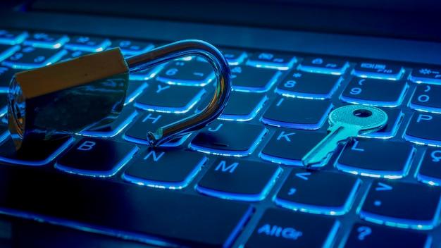 Illuminazione blu della tastiera del notebook con lucchetto e chiave aperti. concetto di tecnologia.