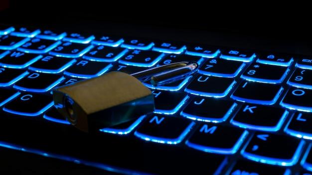 Illuminazione blu della tastiera del notebook con lucchetto aperto concetto tecnologico