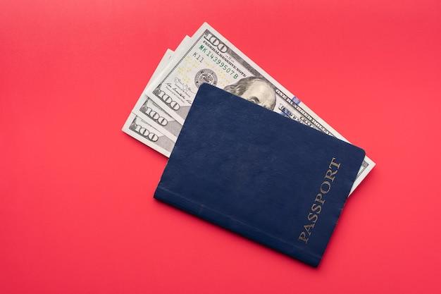 Passaporto internazionale blu e banconote in dollari usa su sfondo rosso, vista dall'alto.