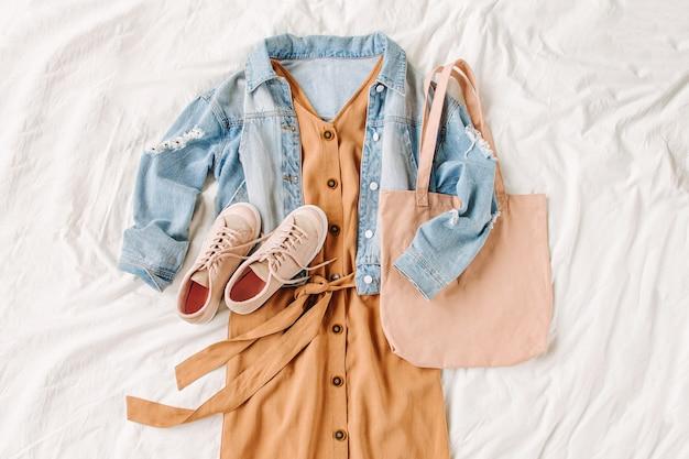 Giacca di jeans blu e abito beige, scarpe da ginnastica con tote bag sul letto bianco. elegante outfit autunnale da donna. vestiti alla moda. disposizione piana, vista dall'alto.