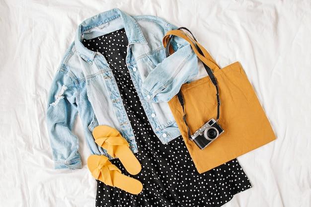 Giacca di jeans blu e abito nero con borsa tote e macchina fotografica sul letto bianco. elegante outfit da donna autunnale o primaverile. vestiti alla moda. disposizione piana, vista dall'alto.
