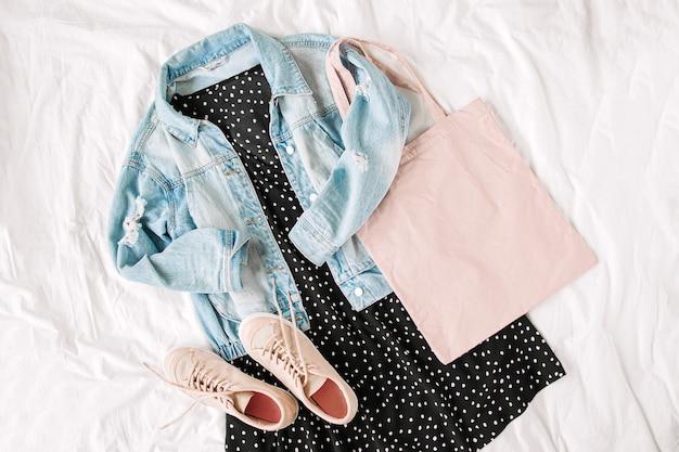 Giacca di jeans blu e abito nero con tote bag sul letto bianco. elegante outfit da donna autunnale o primaverile. vestiti alla moda. disposizione piana, vista dall'alto.