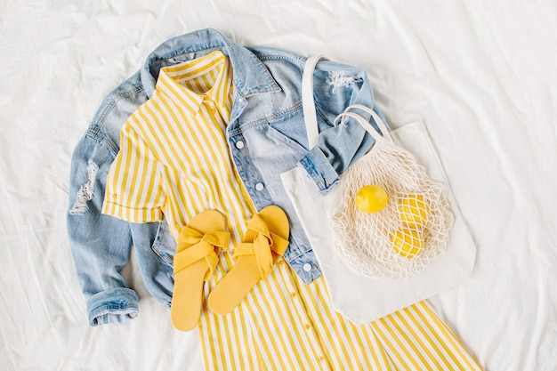 Giacca di jeans blu e vestito giallo con borsa e pantofole sul letto bianco. elegante outfit da donna autunnale o primaverile. vestiti alla moda. concetto di moda. disposizione piana, vista dall'alto.