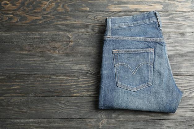 Le blue jeans hanno piegato su un fondo di legno, spazio per testo