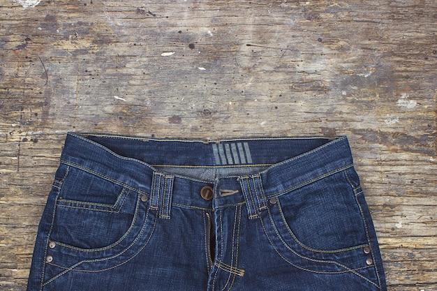 Blue jeans sul vecchio tavolo di legno, piatto disteso. spazio per il testo.