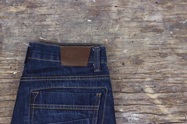 Jeans blu sulla vecchia tavola di legno. spazio per il testo.