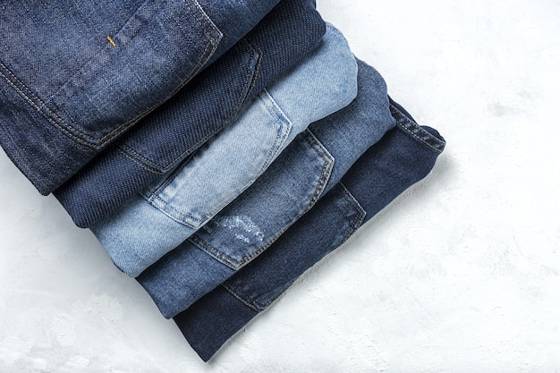 Fondo del mucchio dei vestiti dei pantaloni delle blue jeans. dettaglio di bei blue jeans