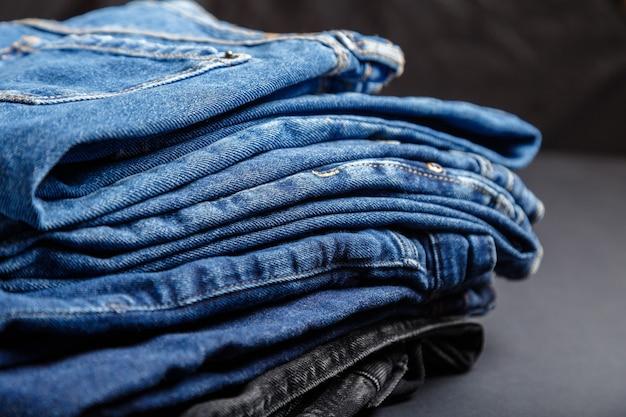 I pantaloni delle blue jeans impilano il fondo del tessuto di struttura del tessuto. pila di varietà di jeans di colore blu, tessuti di jeans denim su sfondo nero.