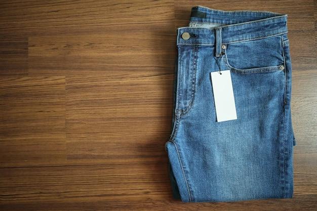 Blue jeans con cartellino del prezzo bianco vuoto sulla tavola di legno