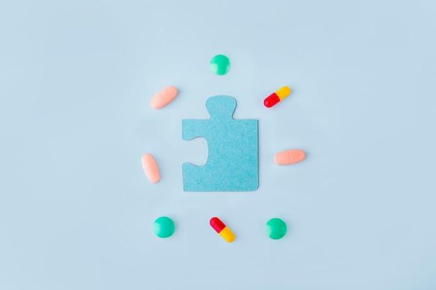 Pezzi di puzzle blu con diverse pillole e medicine. concetto di trattamento delle malattie neurologiche: autismo, morbo di alzheimer, dimensione. copia spazio per il testo. giornata della consapevolezza. sostegno e accettazione.