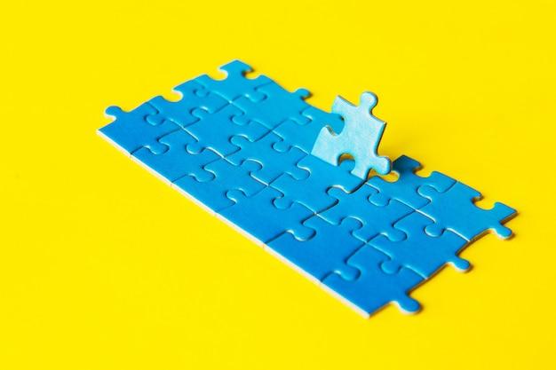Puzzle blu su fondo giallo, rapporto d'affari, successo e concetto di strategia, lavoro di squadra