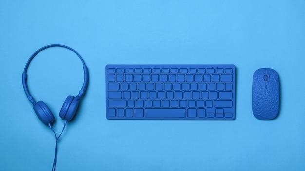 Tastiera, cuffie e mouse blu su sfondo blu. immagine monocromatica di accessori per ufficio.
