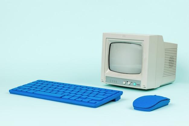 Tastiera e mouse blu e un monitor retrò su sfondo blu. attrezzatura d'epoca.