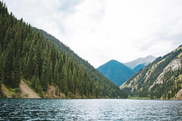 Un lago blu tra montagne e alberi in una giornata estiva.
