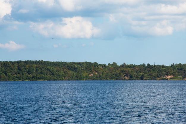Cielo blu del lago blu e foresta sulla riva in una giornata di sole estivo. ricreazione all'aperto