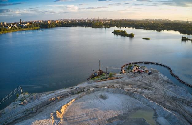 Lago blu, pineta, grande città e bel cielo con nuvole