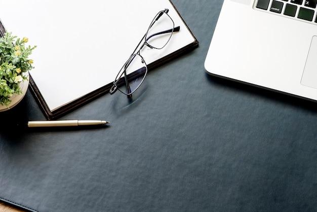 Scrivania in pelle blu con forniture per ufficio e lo spazio della copia.