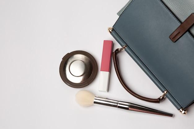 Borsa in pelle blu con evidenziatore, rossetto liquido opaco e pennello su sfondo grigio. spazio per il testo