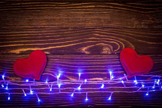 Luci blu con cuori rossi su fondo in legno