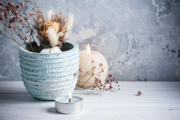Candela accesa blu e fiori secchi in vaso sulla tavola di legno bianca.