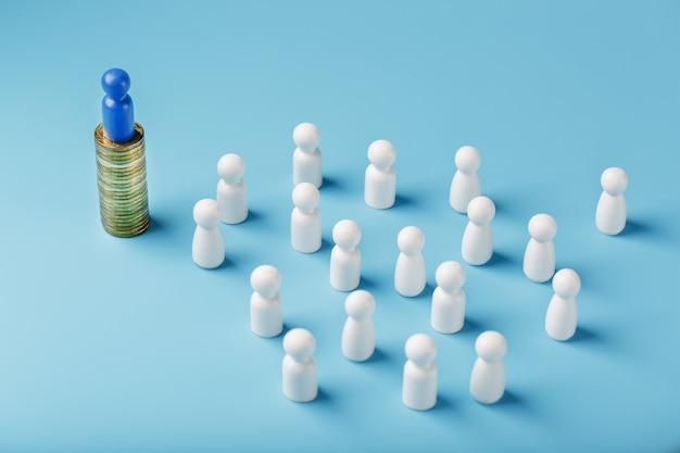 L'uomo blu è in piedi su monete d'oro e controlla una folla di bianchi. il concetto di potere avido e gestione delle persone.