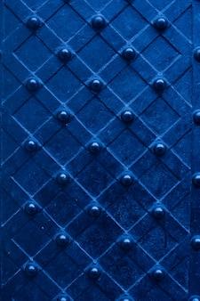 Porta massiccia blu di struttura del metallo con il fondo dei ribattini