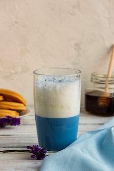 Tè matcha blu in un bicchiere di latte sul tavolo.